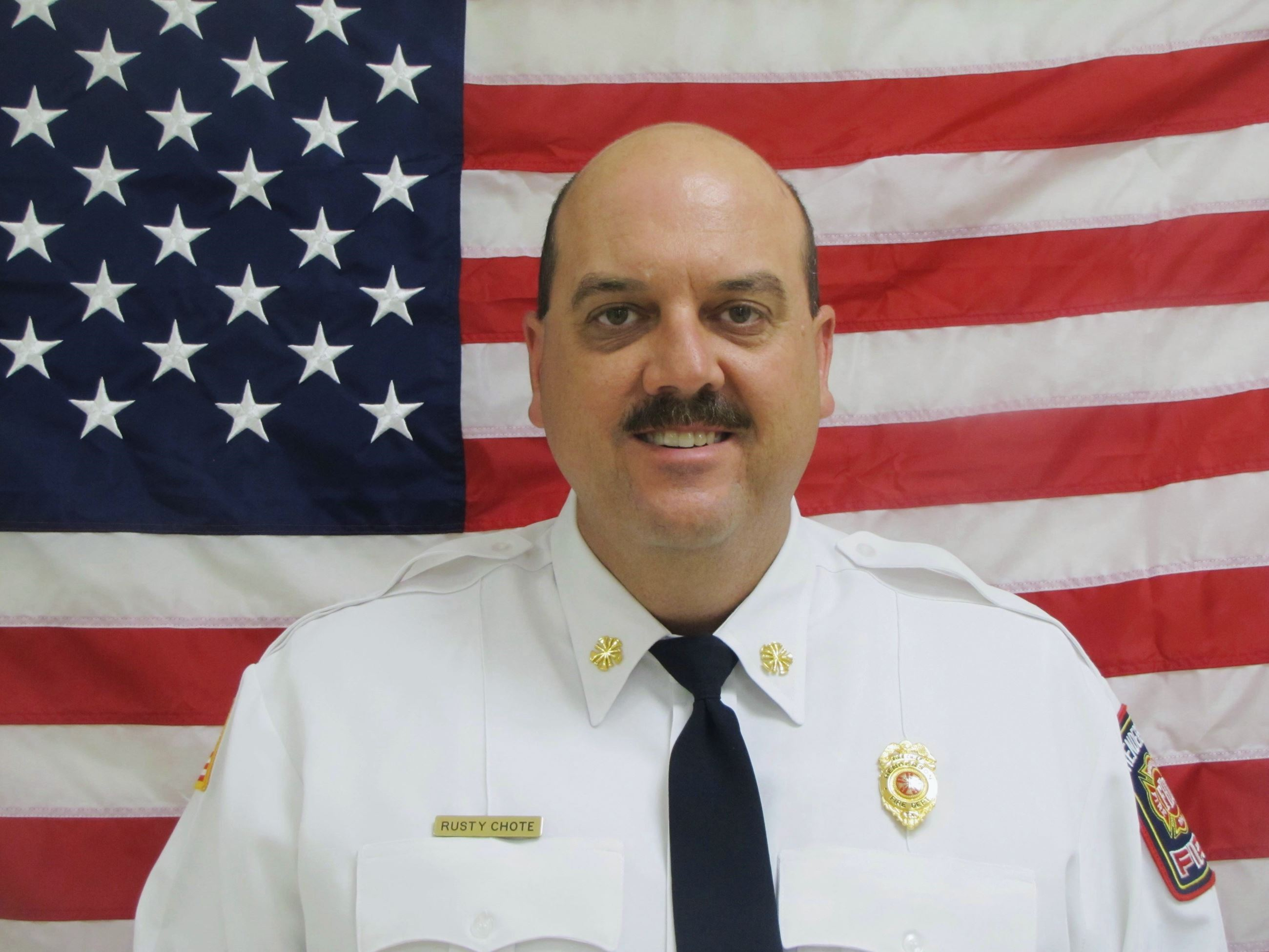 Closeup of Fire Chief Rusty Chote standing in front of American Flag